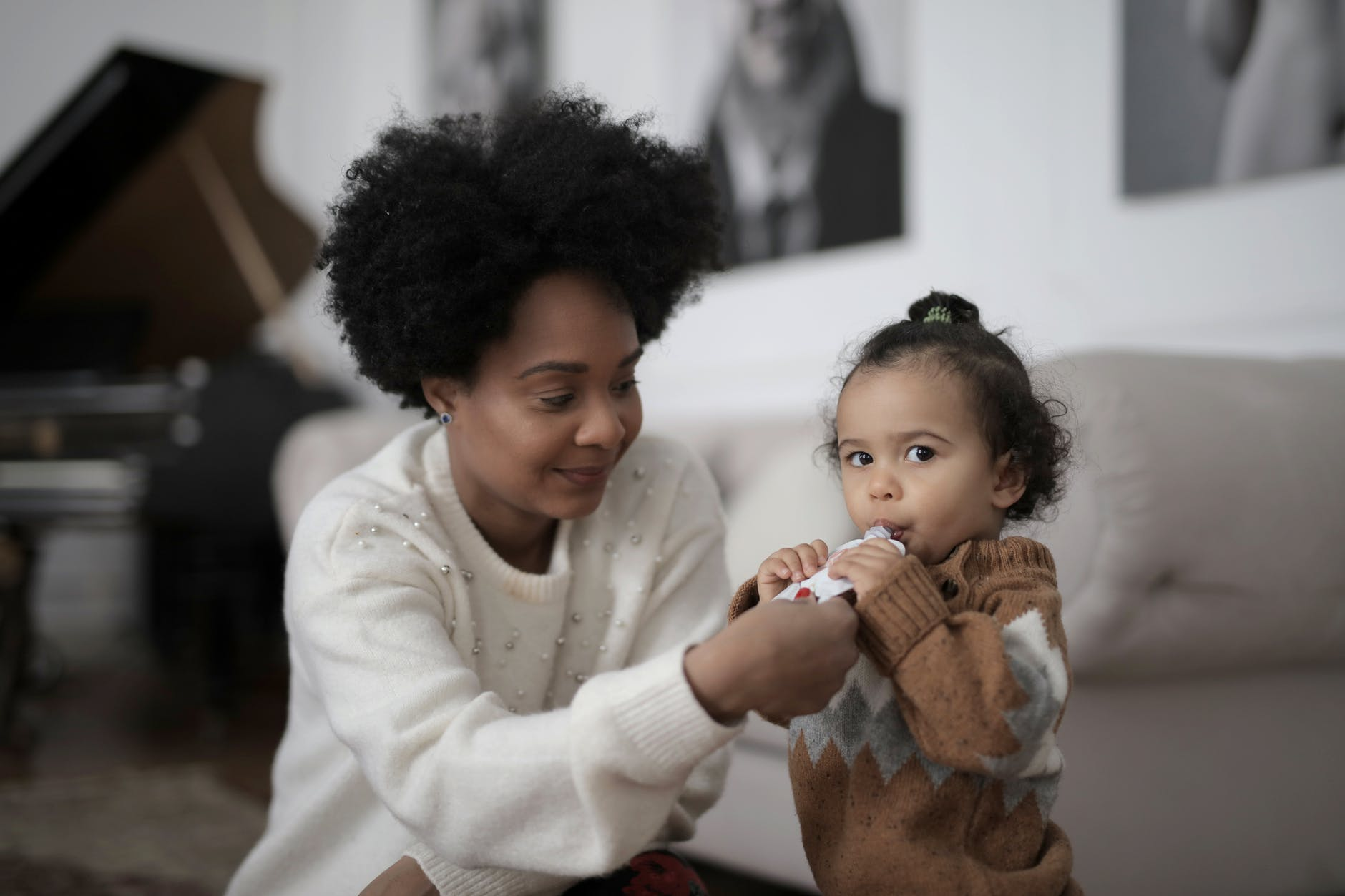 loving african american mother feeding cute daughter with packaged juice at home